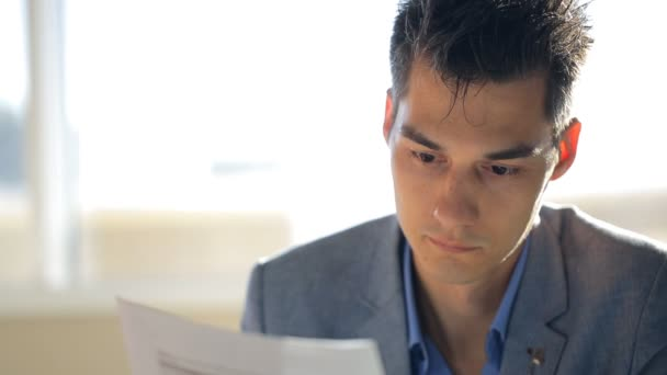 Young and handsome male is reading document sitting in office.