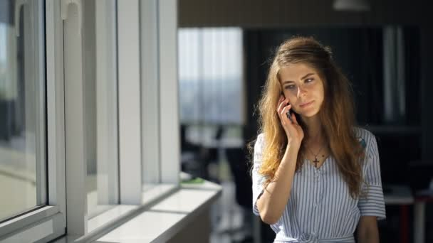 Young and beautiful female is talking on cellphone standing in office corridor.