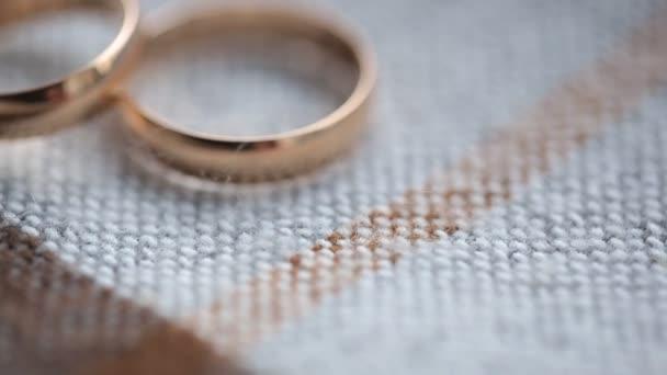 Dva svatební prsteny leží na pletené povrchu ubrus