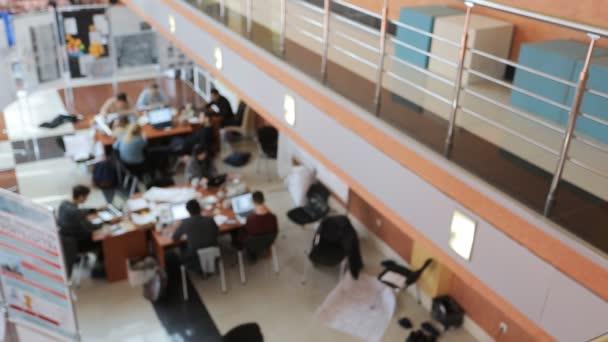 Kolegové sedět u dřevěných stolů a práce na notebooky v denní době