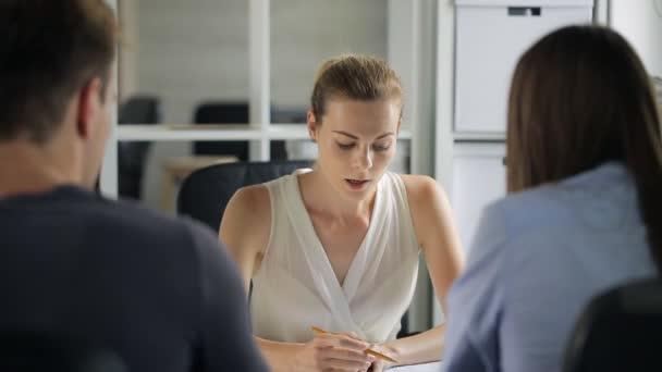 Šéf a podřízenými projednává plány v úřadu.