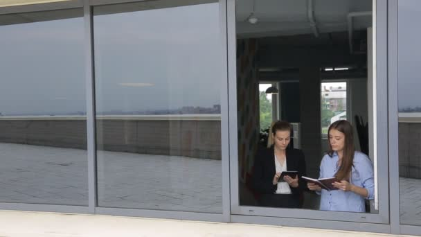 Women are discussing business issues in front of open window.