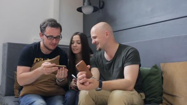 Männer und Frauen schauen im Handy durchs Bild.