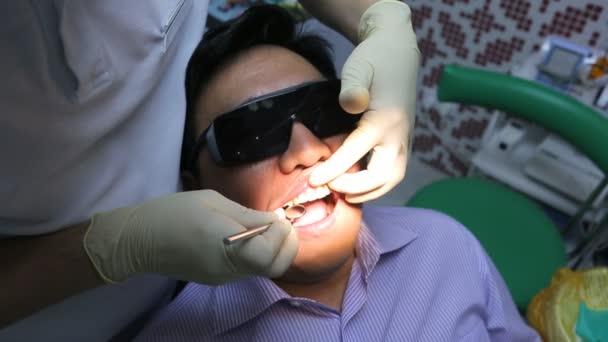 Zubař je léčení klienta zuby v ústech zrcadlo