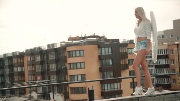 Mladá Američanka kráčí po střeše na pozadí moderních budov ve městě.