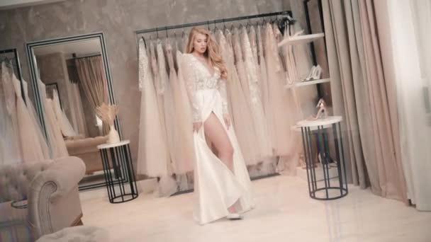 Krásná mladá žena pózuje v bílých svatebních šatech, zatímco stojí v obchodě s oblečením.