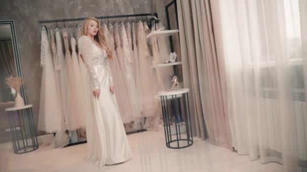 Modell állvány esküvői ruha szalonban, pózol kamera fehér köpenyben. Fiatal nő illik a raktárba