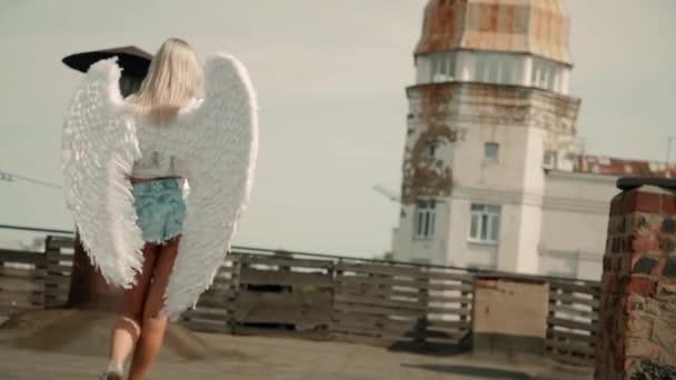 Rückansicht einer Frau in Beuteschüssen und mit weißen Engelsflügeln auf einem verlassenen Stadtdach. Verführerisch