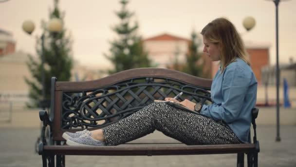 Lány ül egy fa pad, munka az irodában, írja egy notebook, szabadban