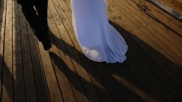 Ženich a nevěsta jdou spolu na molo na svou loď. Její dlouhé bílé šaty. Ruce z nevěsty krásné a jemné kytice jemných květů a jsou to svatební dvojice.