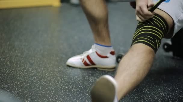 male athletes aged rewinds his knee on the leg hair sport athletic bandage black with yellow stripes, for Security, to load on the joint.