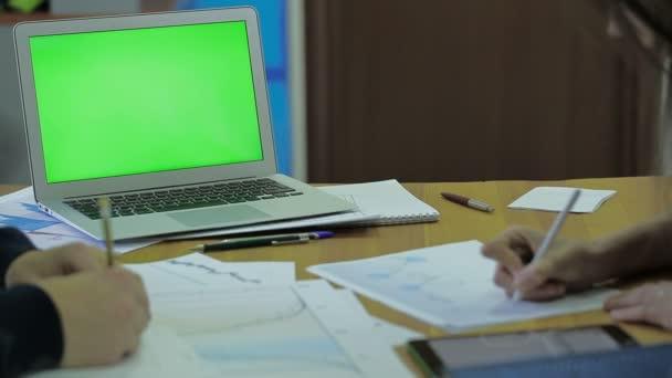 Fa íróasztal és vékony laptop képernyő a Mock up, a hely a szöveg, a dolgozó férfiak és nők a pénzügyi ütemterv tételeket, és így a jel