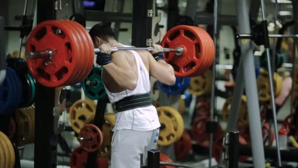 athlete powerlifter sets in the gym a new record one in two hundred pounds kilogram of the dangerous end of the exercise, the bar barely enters into the slots on the rack.