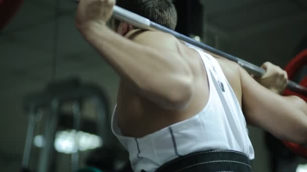 Male athlete powerlifter in the belt for discharge back in the gym at the front squats with a barbell with a lot of pancakes load easily, rapidly, vigorously and without problems.