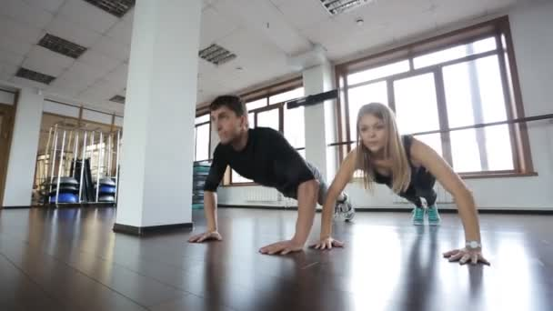 beautiful girl is pushed from the floor next to his coach, man. She athlete fintnes instructor
