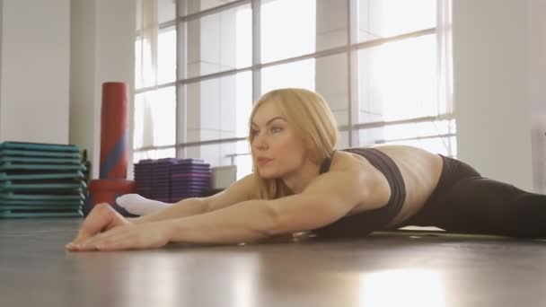 A blonde woman athlete doing stretching in the gym  while in the splits she  stretches forward