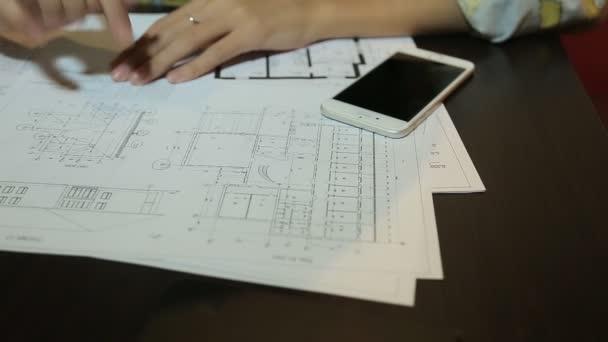 Žena architekt s blueprint listy, rozložení a výkresy budov