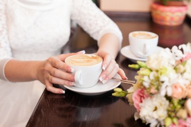 bride holds a cup of coffee in hand