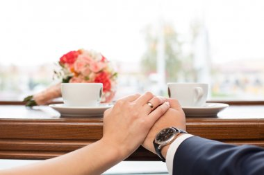 newlyweds behind show-window in cafe and  cup of coffee