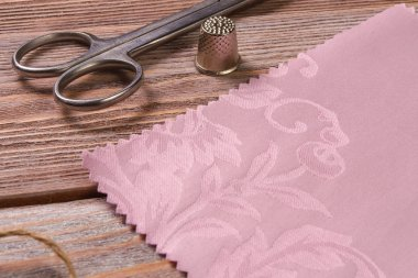 Textiles on a vintage wooden table with scissors and thimble