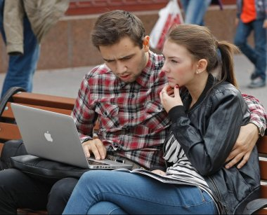 Young man and woman working with laptop in park