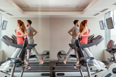 People running on treadmills in gym