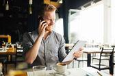 Zaneprázdněný blogger multitasking v kavárně