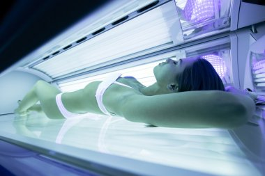 Beautiful woman tanning in solarium