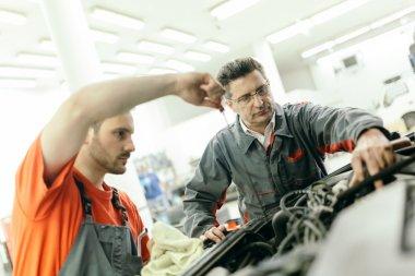 Car mechanics fixing car in garage - teamwork stock vector