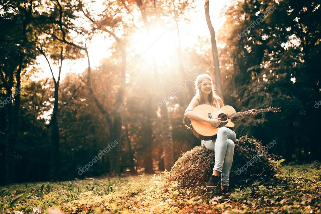 Beautiful hippie playing  guitar