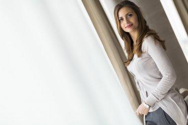 Beautiful brunette posing in front of a window