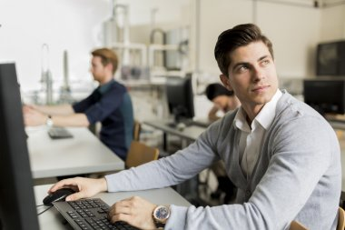 Young handsome student using computer