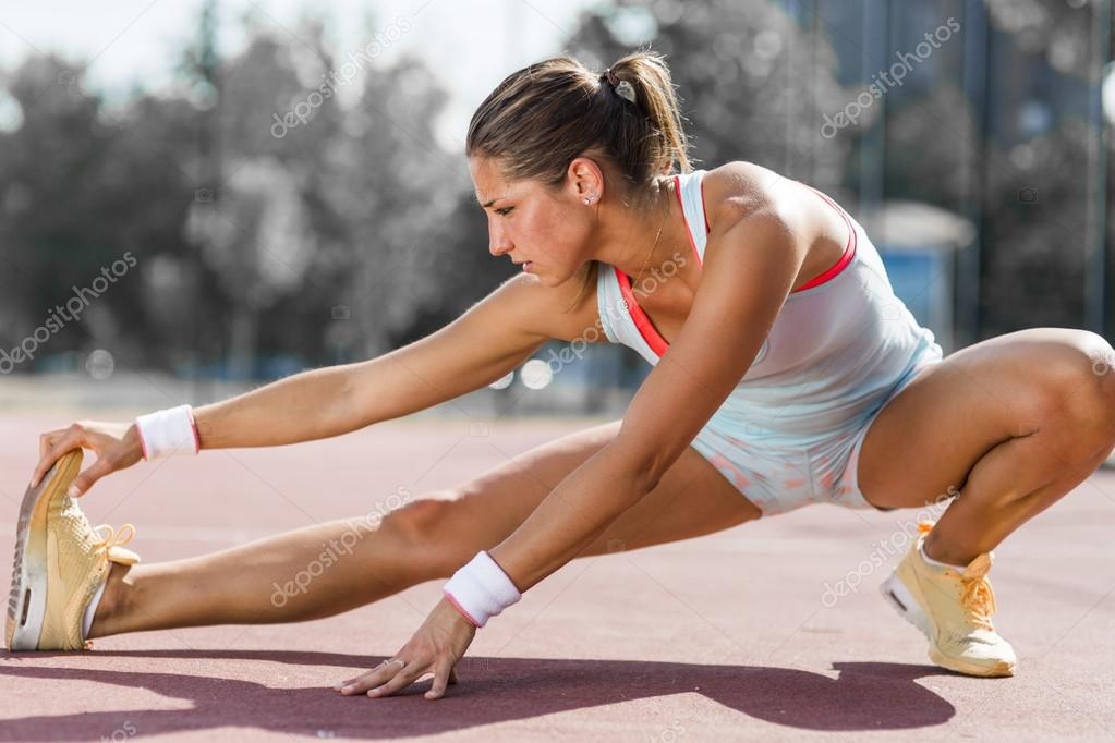 Athletic woman stretching in summer
