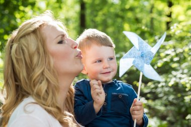 Womanwith her son a blowing the paper windmill