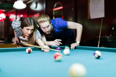 Man and woman flirting while playing snooker