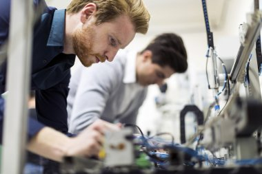 Two young handsome engineers working on electronics components and fixing broken chips stock vector