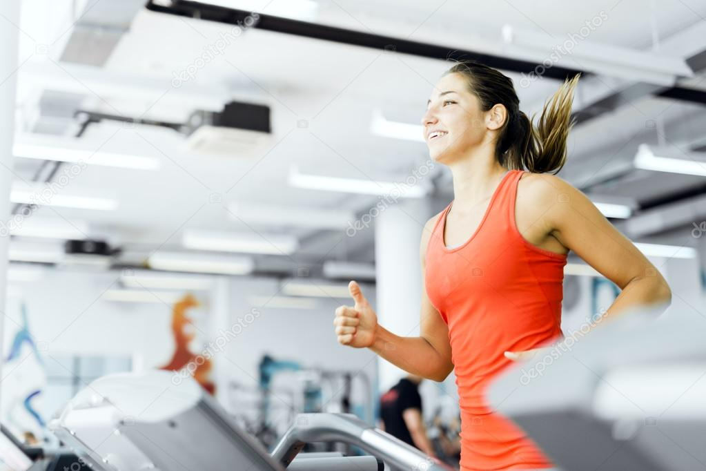 Woman running on a treadmill in gym