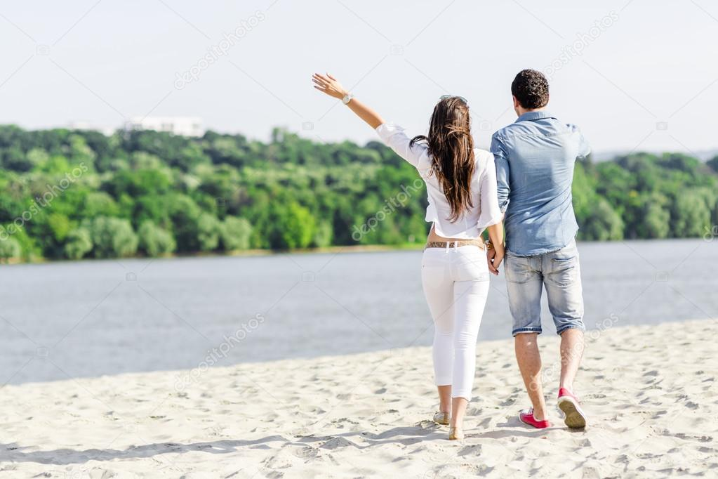 Couple holding hands and walking on a beach