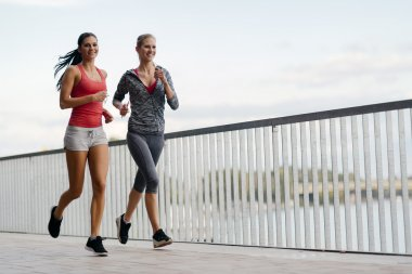 Two sporty women jogging in city
