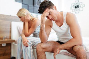 Worried couple having problems in bedroom