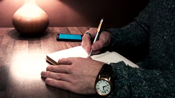 Kezét az asztalra egy smartphone és ír egy tollal a jegyzetfüzet