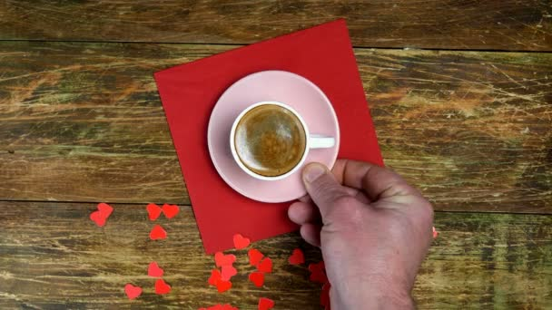 Az emberi kezek egy csésze kávét és Teddy macit tettek a piros szalvétára. Vörös szívek. Romantikus nap. Valentin-napi vagy női napi koncepció. Első látásra. Lapos fekvés. Közelkép.