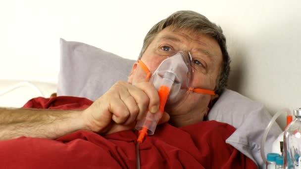 Kranker Mann mittleren Alters atmet im Bett durch eine Sauerstoffmaske. Behandlung von Asthma, Allergien, Bronchitis, Lungenentzündung bei Covid-19 und Atemwegserkrankungen. Nahaufnahme. Innenräume.