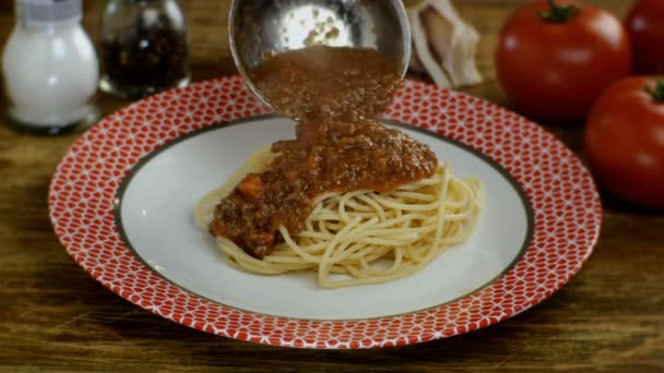 Bolognese sauce putting in cooked spaghetti or tagliatelle pasta in white plate, in restaurant or home kitchen. Sprinkles parmesan. Homemade recipe cooking.