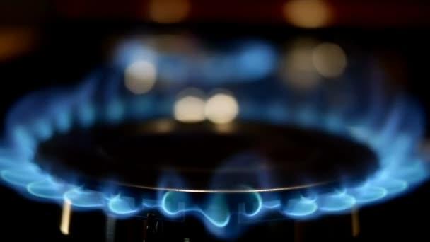 Prozess der Verbrennung und des Auftretens einer blauen Flamme von Gas Methan oder Propan auf einem Küchengasherd. Küchenherd umstellen. Erdgasentzündung. Selektiver Fokus. Zeitlupe. Nahaufnahme.