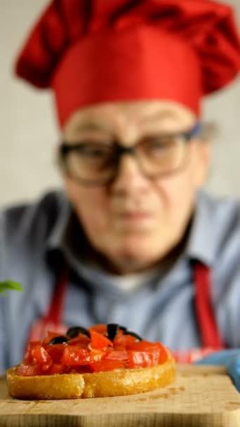 Starší dospělý kuchař Kavkazský etnický původ v červené čepici zdobí bruschettu bazalkovými rajčaty v domácí kuchyni. Soustřeď se. Selektivní soustředění. Umělecké rozmazané pozadí.