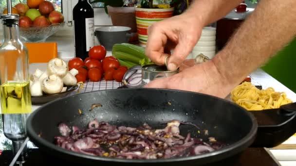 Stůl v kuchyni. Příprava středomořských potravin. Smažená pánev s nakrájenou cibulí. Šéfkuchař přidá konzervovaná rajčata na výrobu omáčky s kuřecím masem, cibulí, celerem, houbami. Detailní záběr.