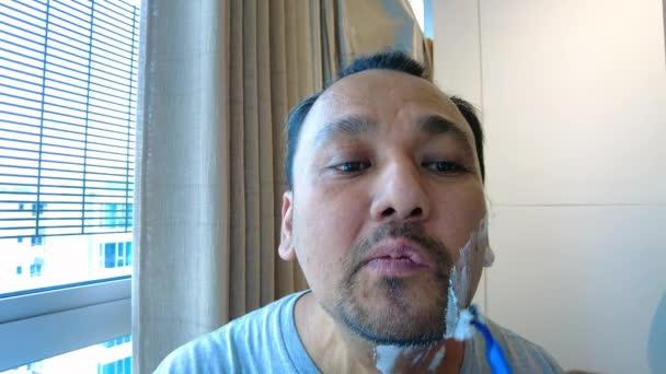 Asian man carefully shaving his face with blue razor.