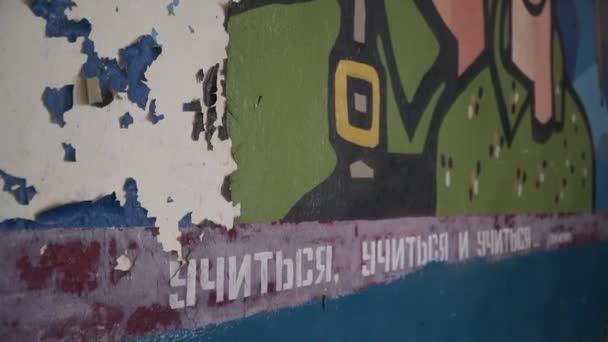 starý obrázek na zdi, chlap a holka v zeleném, raketa v pozadí. hala opuštěné školy / pohled zezdola nahoru / Rusko