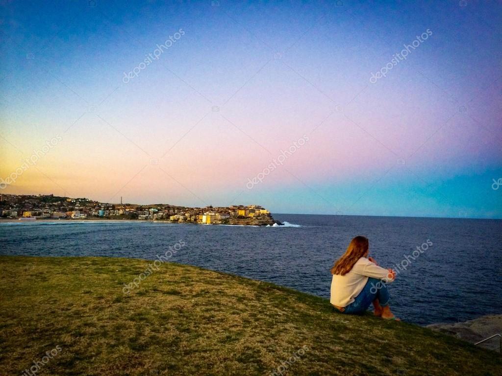 Alone girl on shore of ocean
